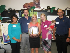 Credit union team members, including two of Mrs. Sauser's former students, present her with the Appreciated Teacher Award.